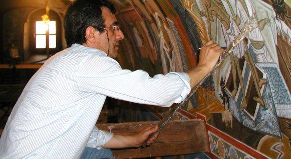 Markos Kampanis painting a mural